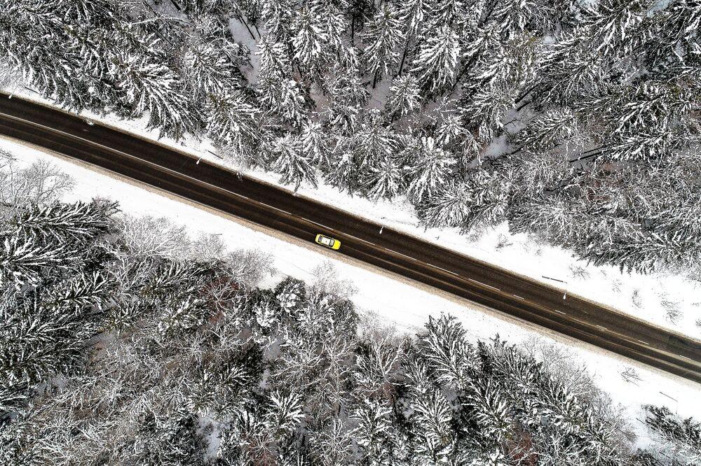 سيارة تسير على طول الطريق السريع عبر غابة تريوتسكي في منطقة ترويتسك الإدارية في موسكو