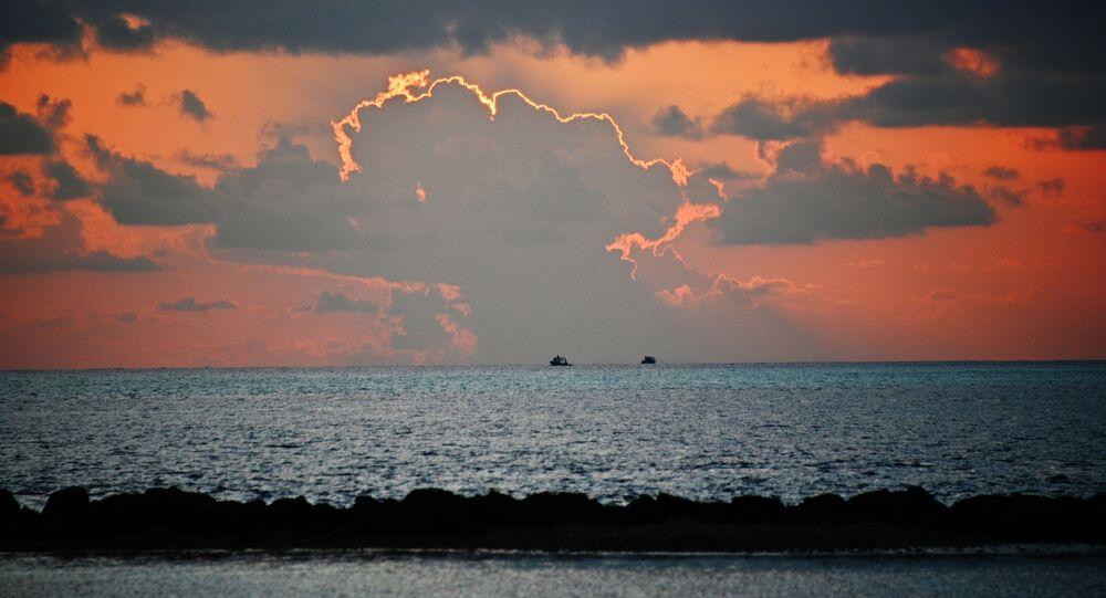 منظر يطل على البحر من شاطئ أحد جزر المالديف عند غروب الشمس