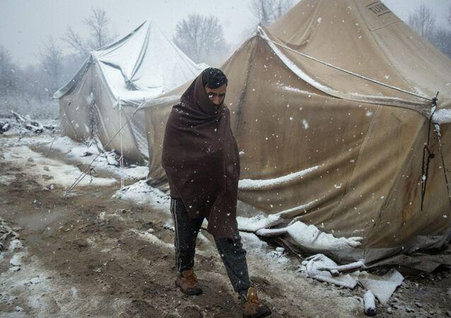 رجل، لاجئ، يسير بين خيام للاجئين بالرغم من بدء البرد وتساقط الثلج في مخيم للاجئين فوجاك، شمال غرب البوسنة، 2 ديسمبر 2019