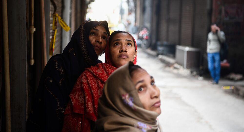 نساء ينظرن إلى حريق في مصنع في نيودلهي، الهند 9 ديسمبر 2019