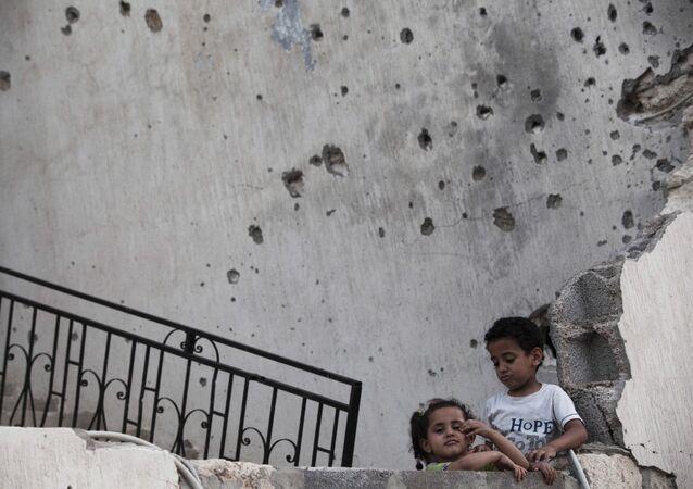 أطفال في ليبيا وفي الخلفية أثار طلقات الرصاص