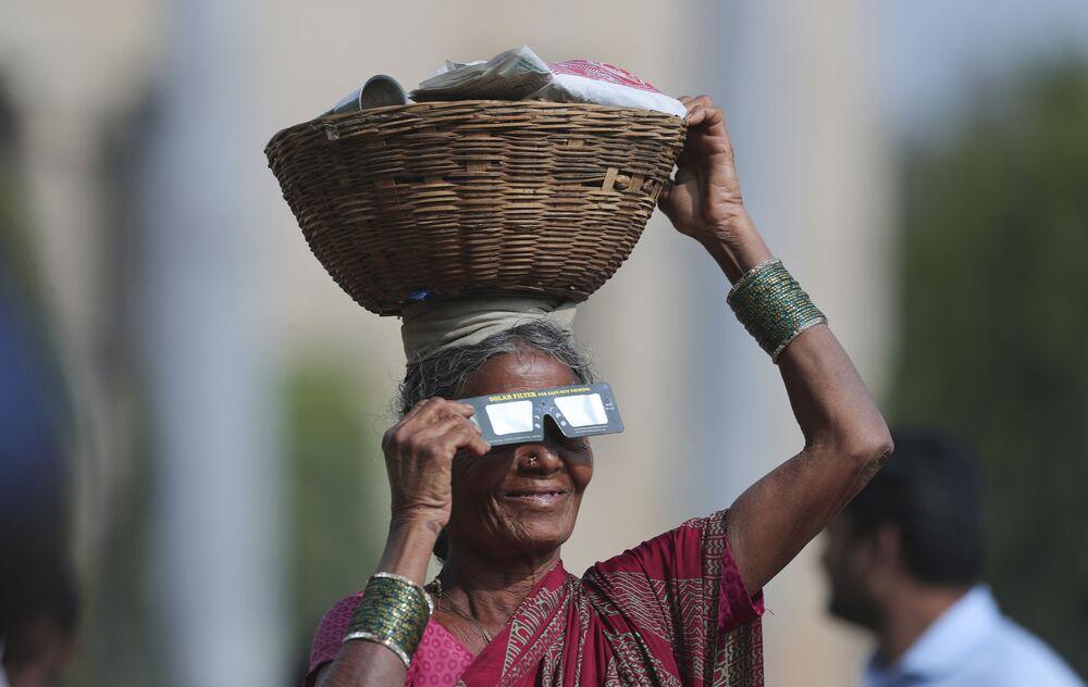 بائعة متجولة تحمل نظارات خاصة وتشاهد كسوف شمسي جزئي في حيدر آباد، الهند 26 ديسمبر 2019