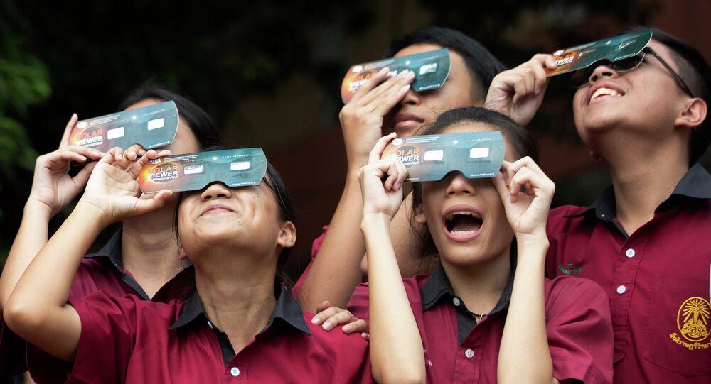 تلاميذ يشاهدون كسوف الشمس عبر نظارات خاصة في مدرسة سانتيراويذايالي في بانكوك، تايلاند 26 ديسمبر 2019