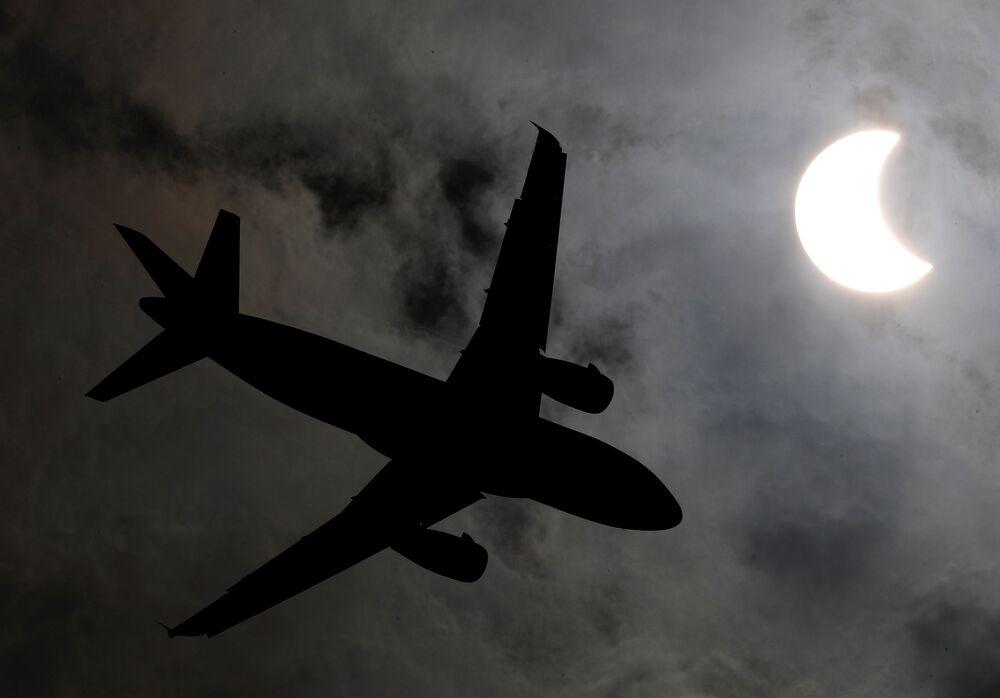 طائرة تحلق على خلفية كسوف الشمس في بانكوك، تايلاند 26 ديسمبر 2019