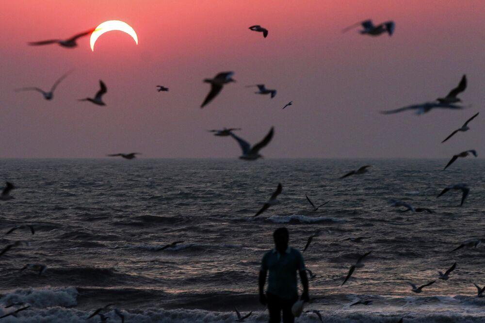 رجل على شاطئ البحر في الكويت خلال كسوف جزئي، 25 ديسمبر 2019