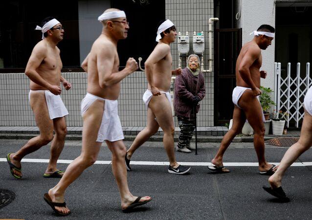 امرأة تنظر إلى رجال يبانيون يركضون حول معبد تيبوزو إنراي، استعدادا للسباحة في المياه الجليدية في إطار مراسم تطهير الروح وتمنياتهم بصحة جيدة في العام الجديد في طوكيو، اليابان 12 يناير 2020