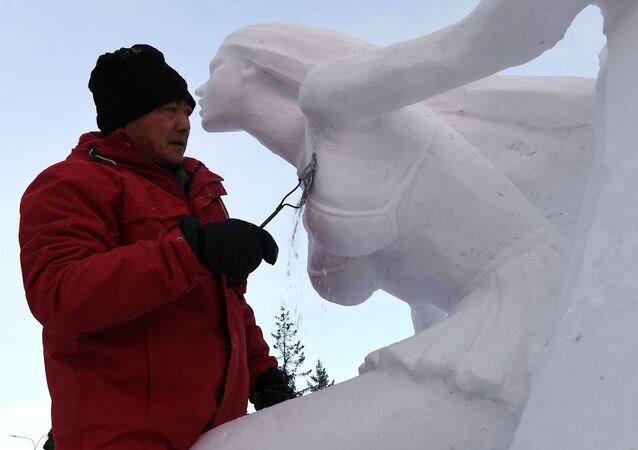 الفائز في الفئة المرشحة الثلج يعمل على منحوتة ثلجية في المهرجان الدولي السنوي الثامن للثلوج والمنحوتات الثلجية في كراسنويارسك الروسية، 17 يناير 2020