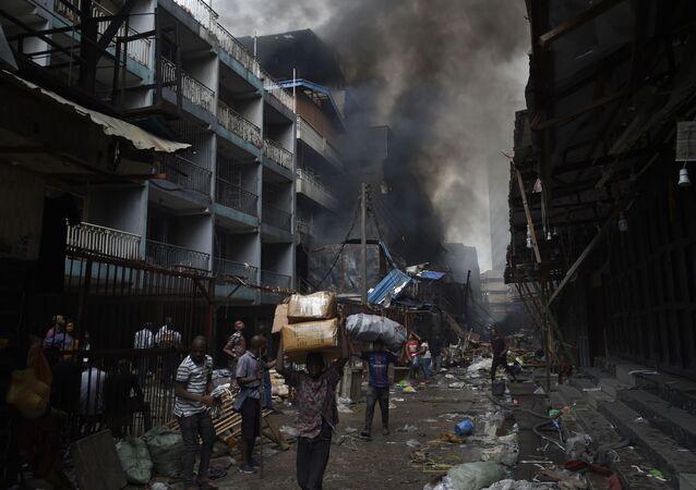 أهالي حي سوق بالوغون في لاغوس يحملون أغراضهم بعد أن تم اطفاء الحريق في المنطقة، نيجيريا 29 يناير 2020