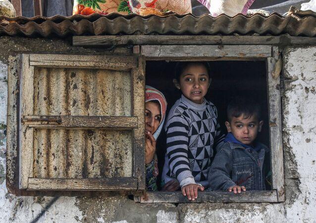 عائلة فلسطسنية في مخيم اللاجئين في خان يونس تطل من نافذة، جنوب قطاع غزة، فلسطين 28 يناير 2020