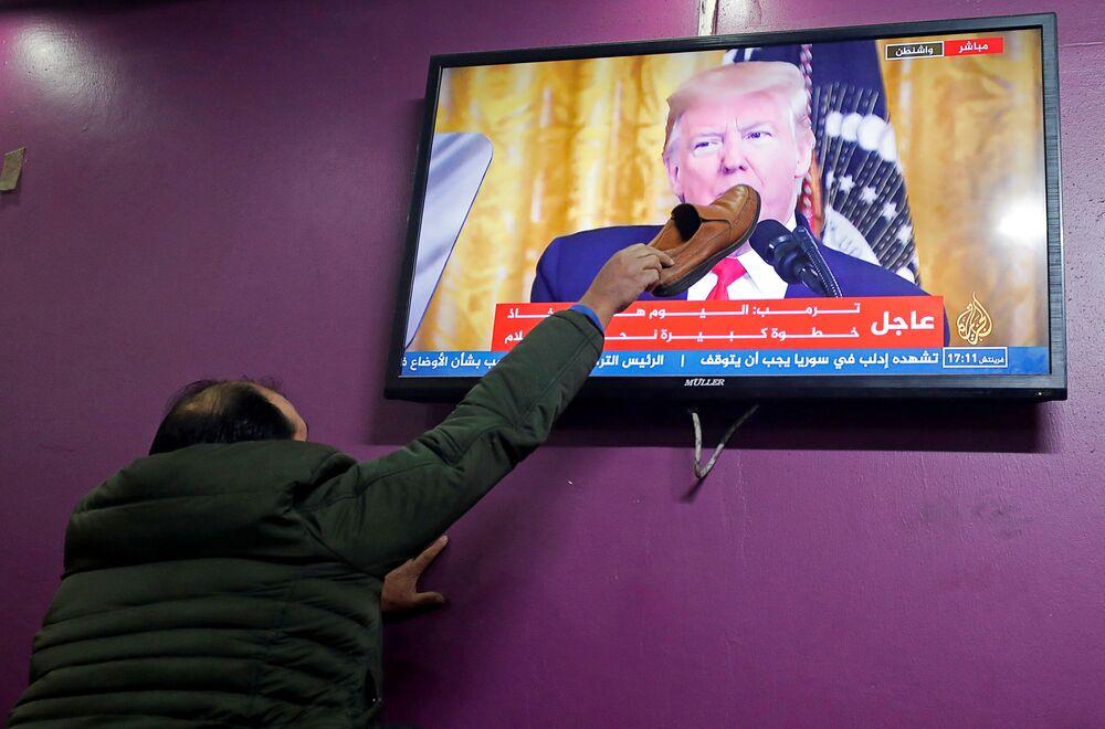 فلسطيني يضع حذاءًا على شاشة تلفزيون في مقهى في الخليل، خلال إعلان الرئيس الأمريكي دونالد ترامب لـصفقة القرن، الضفة الغربية 28 يناير 2020