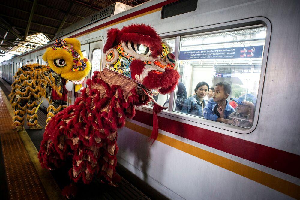 ينظر الركاب عبر نافذة القطار إلى التنانين في محطة غامبير خلال احتفالات السنة القمرية الصينية الجديدة في جاكرتا، إندونيسيا 25 يناير 2020
