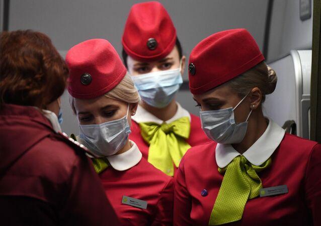 مضيفات رحلة الطيران S7 القادمة من بكين في مطار تولماتشيوفا في نوفوسيبيرسك الروسية، 28 يناير 2020