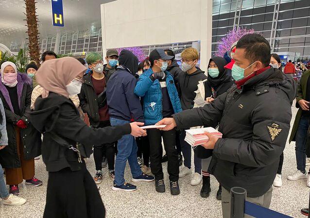 مواطنون إندونيسيون ينتظرون إجلاؤهم من مدينة ووهان الصينية، قبل المغادرة إلى بلادهم في مطار تيانخه الدولي