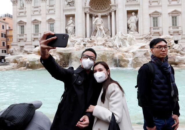 سياح يرتدون أقنعة واقية بعد تأكيد حالات الإصابة بفيروس كورونا في إيطاليا، يلتقطون صورة سيلفي أمام نافورة تريفي في روما، 31 يناير 2020