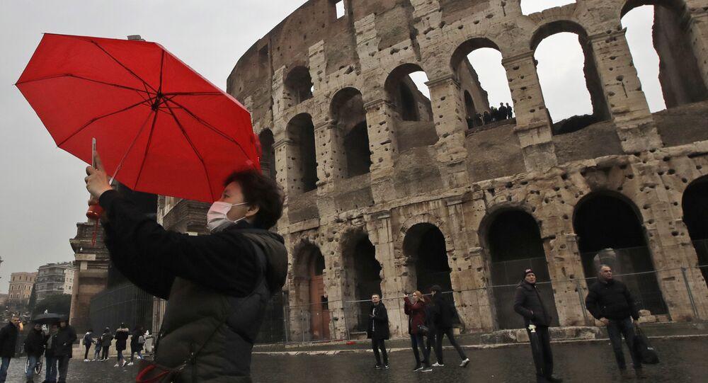 سياح يرتدون أقنعة واقية بعد تأكيد حالات الإصابة بفيروس كورونا في إيطاليا، يلتقطون صورة سيلفي على خلفية  كولوسيوم في روما، 1 فبراير 2020