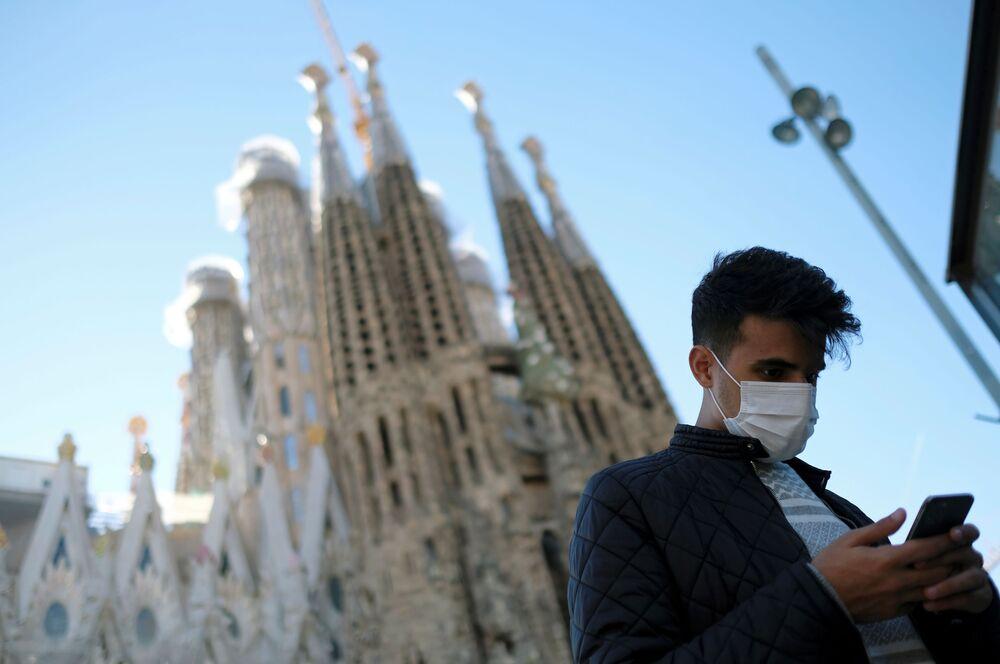 سائح صيني يرتدي قناعا واقيا بعد تأكيد حالات الإصابة بفيروس كورونا في إسبانيا، يلتقط صورة على خلفية كنيسة العائلة المقدسة في برشلونة (باسيليكا ساغري غدا فاميليا) 2 فبراير 2020