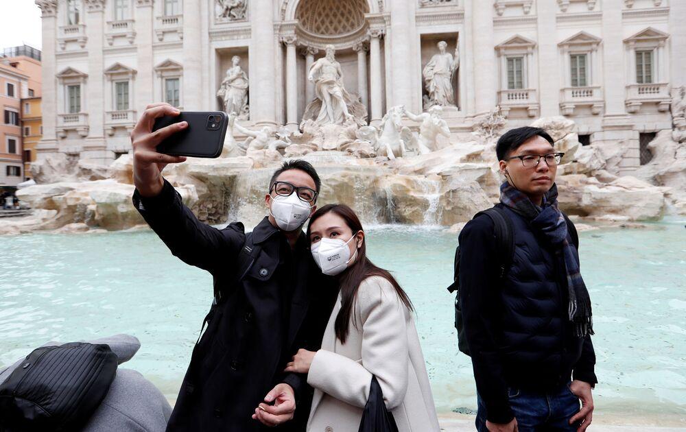سياح يرتدون أقنعة واقية بعد تأكيد حالات الإصابة بفيروس كورونا في إيطاليا، يلتقطون صورة سيلفي على خلفية نافورة تريفي في روما، 31 يناير 2020