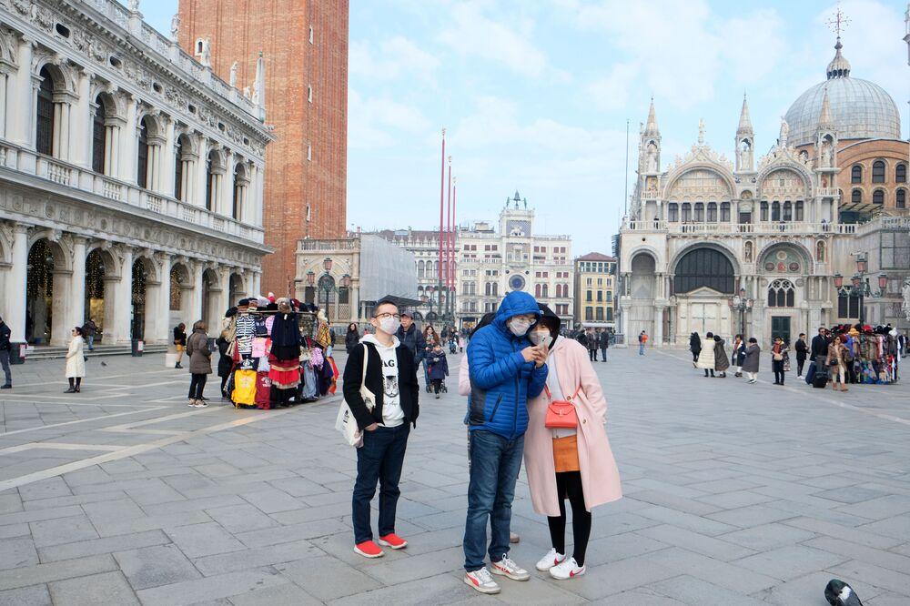 سياح صينيون يرتدون أقنعة واقية بعد تأكيد حالات الإصابة بفيروس كورونا في إيطاليا، يلتقطون صورا في ساحة القديس مرقس (سان ماركوس)، 31 يناير 2020