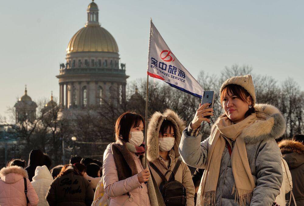 سياح صينيون يرتدون أقنعة واقية، يلتقطون صورا في سان بطرسبورغ، 23 يناير 2020