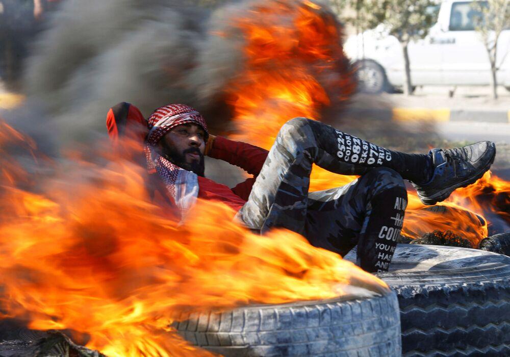 متظاهر بين الإطارات المشتعلة التي تسد الطريق خلال الاحتجاجات المناهضة للحكومة في مدينة النجف العراقية، 2 فبراير 2020