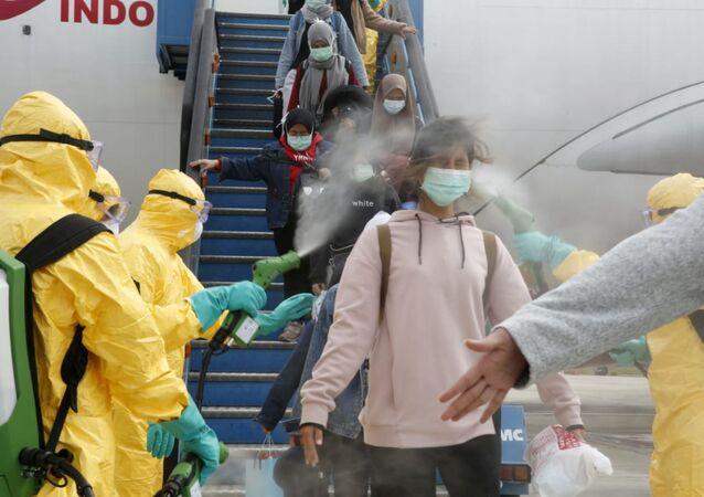 أطباء يقوم برش مطهر طبي على مواطنين إندونيسيين بعد وصولهم من مدينة ووهان الصينية، 2 فبراير 2020