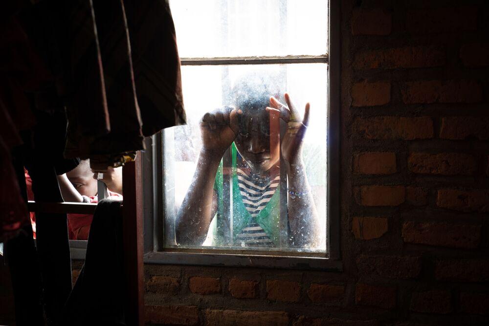 فتاة تنظر عبر نافذة مركز للمهاجرين في نيروشيشي، رواندا 31 يناير 2020