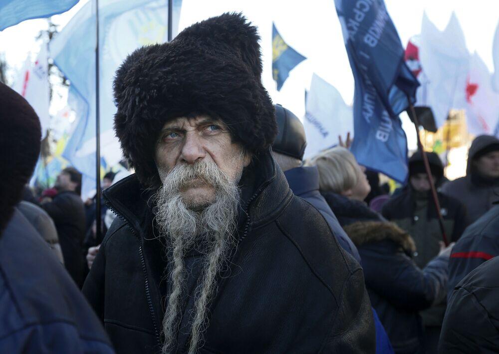 أحد الحتجين أمام مبنى البرلمان ضد التغييرات في القوانين التي تحكم بيع الأراضي الزراعية، في مدينة كييف الأوكرانية، 6 فبراير 2020. اندلعت مشاجرات داخل البرلمان فيما ناقش المشرعون تغييرات على القوانين المقيدة مبيعات الأراضي الزراعية.
