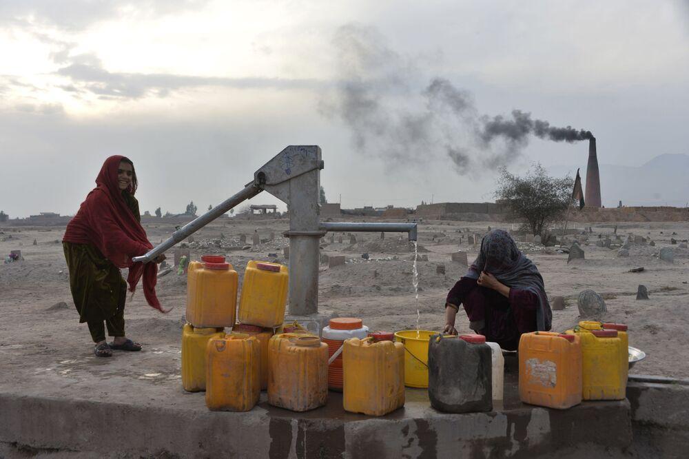 امرأة تضخ الماء من بئر بالقرب من مدينة جلال آباد الأفغانية، 3 فبراير 2020