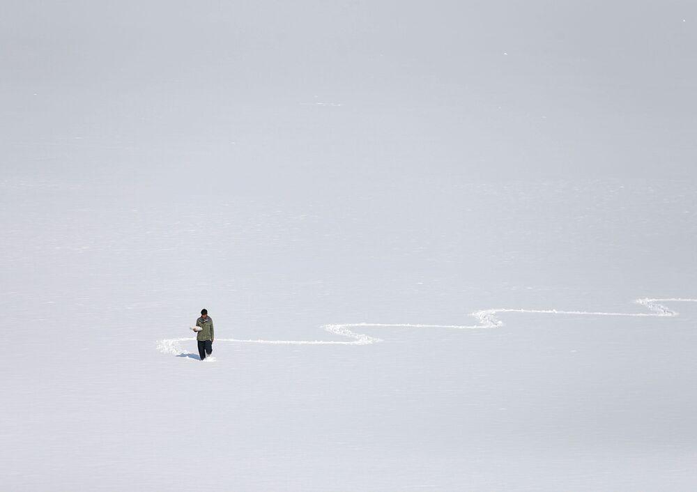 رجل أفغاني يحمل بيضًا مسلوقًا للبيع يعبر بحيرة قارغا (قرغه) المغطاة بالثلوج في كابول، أفغانستان 4 فبراير 2020