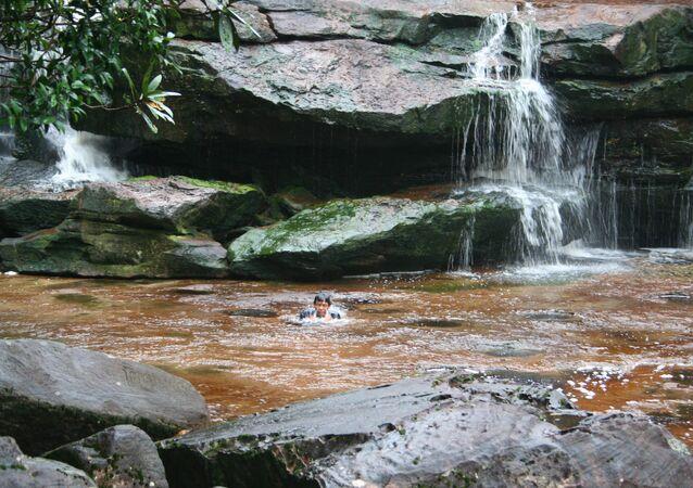 رجل أثناء السباحة تحت شلال في كمبوديا