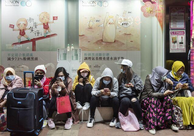 نساء يرتدين أقنعة واقية في أحد شوارع هونغ كونغ، كورونا