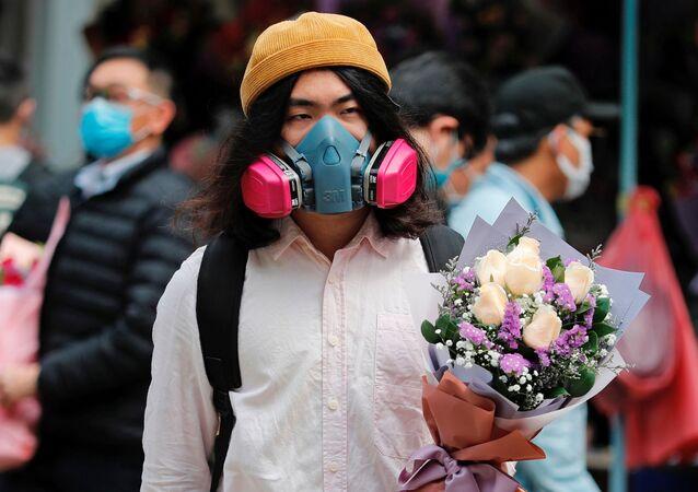 رجل يرتدي قناعا واقيا ويحمل باقة زهور بمناسبة يوم فالنتاين (عيد الحب) في هونغ كونغ، الصين 14 فبراير 2020