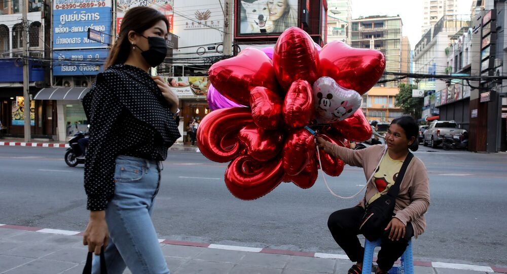 امرأة ترتدي قناعا واقيا تسير على خلفية بلالين على شكل قلوب حمراء في بانكوك، تايلاند 14 فبراير 2020