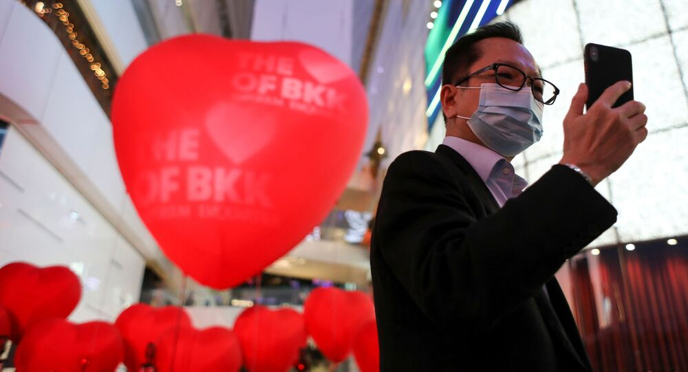 رجل يرتدي قناعا واقيا يلتقط صورة سيلفي على خلفية بلالين على شكل قلوب حمراء بمناسبة يوم فالنتاين (عيد الحب) في بانكوك، تايلاند 13 فبراير 2020