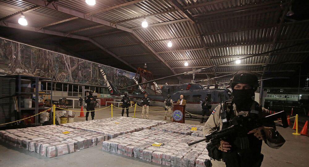 ضابط شرطة أمام طرود تحتوي كوكايين مضبوط خلال عملية في منطقة البحر الكاريبي