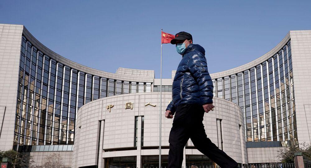 رجل يرتدي قناعًا يمر أمام مقر بنك الشعب الصيني - البنك المركزي في الصين