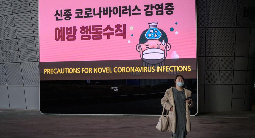 امرأة ترتدي قناعًا أمام شاشة تعرض تدابير وقائية ضد فيروس كورونا الجديد - كوريا الجنوبية