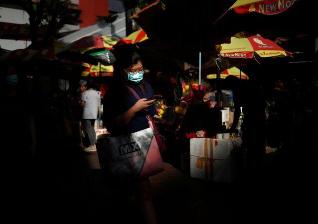 سيدة ترتدي كمامة واقية من فيروس كورونا المستجد وتحمل في يدها باقة زهور خارج معبد كوان إيم هود تشو في سنغافورة