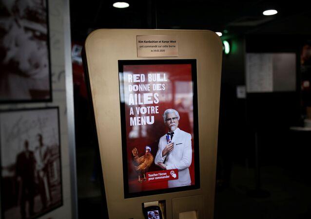 لوحة مطلية بالذهب على كشك طلبات في أحد فروع مطاعم دجاج كنتاكي في العاصمة الفرنسية، يؤرخ لزيارة كيم كارداشيان وزوجها كانيى ويست، بتاريخ 19 فبراير/ شباط 2020