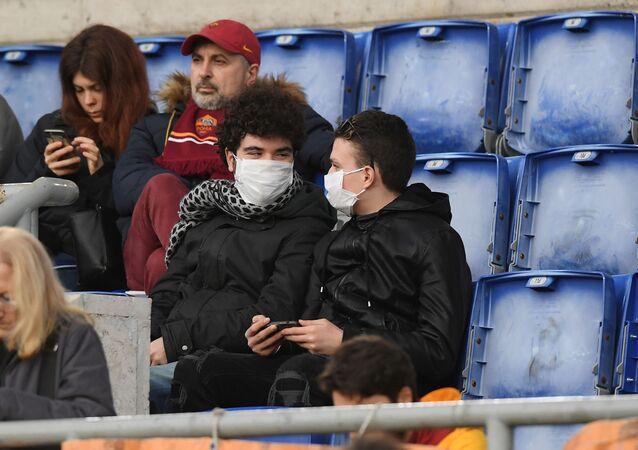 مواطنون إيطاليون يرتدون كمامات واقية من فيروس كورونا خلال إحدى مباريات الدوري الإيطالي الكالتشيو