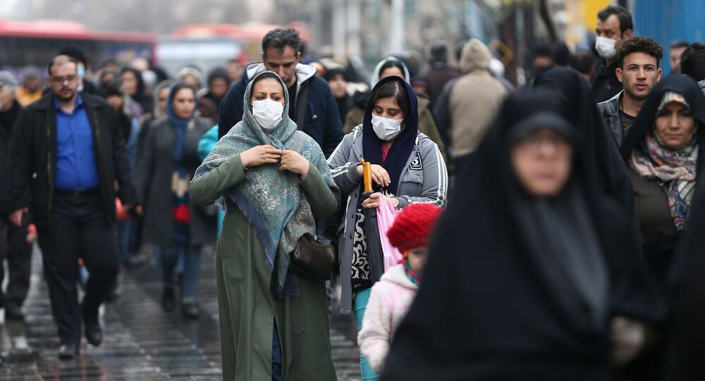 مواطنات إيرانيات يرتدين كمامات واقية من فيروس كورونا خلال سيرهن في أحد شوارع طهران