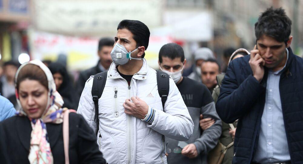 مواطنون إيرانيون يرتدون كمامات واقية من فيروس كورونا خلال سيرهم في أحد شوارع طهران