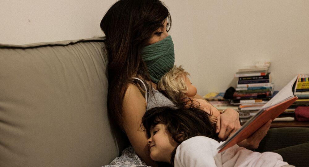 أم وابنتها يجلسون على أريكة في منزل داخل أحد المناطق المصابة بفيروس كورونا في الصين