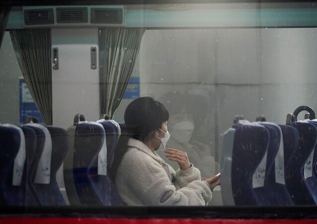 امرأة ترتدي كمامة واقية من فيرووس كورونا تجلس داخل قطار في محطة سكة حديد سيئول فبراير / شباط 2020