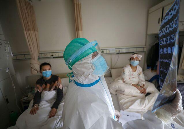 طبيب يتفقد الآشعة المقطعية لمرضى بفيروس كورونا في مدينة ووهان الصينية