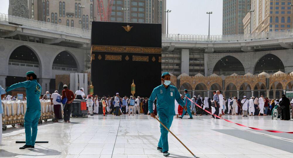 عمال النظافة يرتدون كمامات طبية، أثناء مسحهم للأرض في الكعبة المشرفة في المسجد الحرام في مدينة مكة المكرمة، المملكة العربية السعودية، في أعقاب انتشار فيروس كورونا المستجد، 3 مارس/ آذار 2020