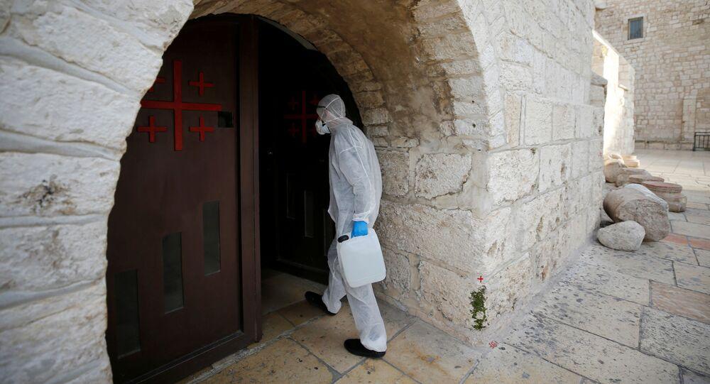 عامل يرتدي بدلة واقية يصل لتطهير كنيسة المهد كإجراء وقائي ضد فيروس كورونا في بيت لحم في الضفة الغربية التي تحتلها إسرائيل