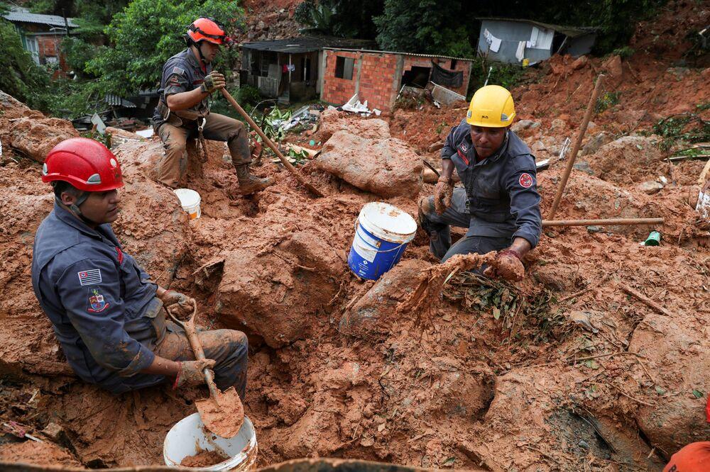 رجال الانقاذ يبحثون عن ضحايا الانهيار الأرضي الناجم عن الأمطار الغزيرة في مدينة غوارويا الساحلية في البرازيل، 3 مارس 2020