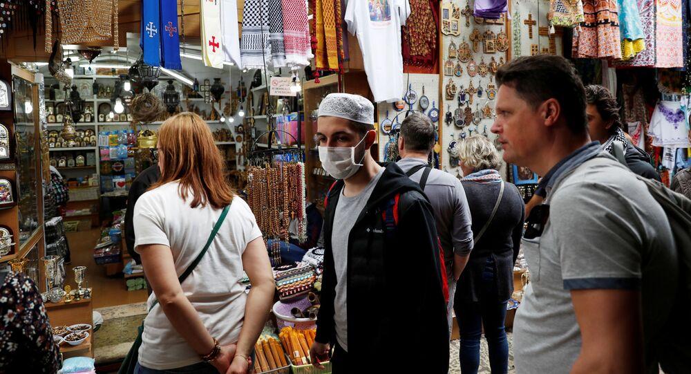 شخص يرتدي كمامة واقية من فيروس كروونا (كوفيد-19) بينما يسير في مدينة القدس