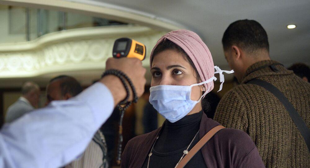 امرأة ترتدي كمامة طبية وتخضع لفحص درجة حرارة جسدها على متن قارب سياحي في مدينة الأقصر بجنوب مصر، للكشف عن فيروس كورونا المستجد، 8 مارس/ آذار 2020